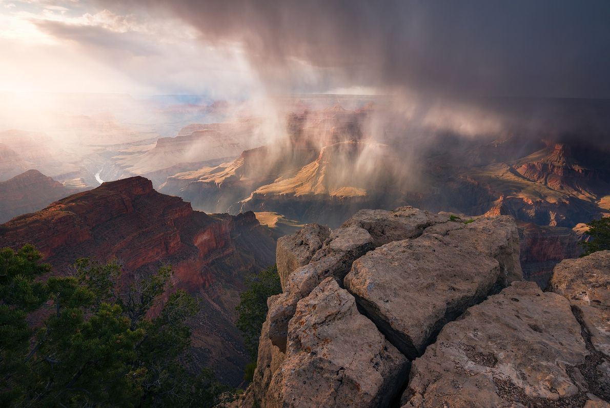 Un rideau de pluie diffuse les rayons du soleil qui inondent le canyon en contrebas du ...