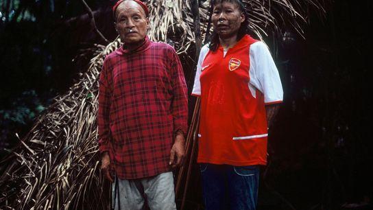Shuri et sa femme Janet posent devant leur maloca, abri fait de feuilles de palmier, en ...