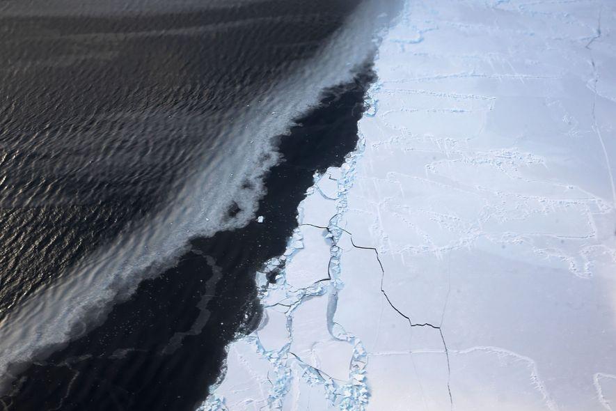 La glace flotte près de la côte ouest de l'Antarctique vue depuis la fenêtre d'un avion ...