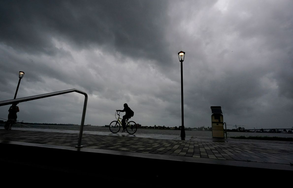 Un homme fait du vélo le long du Mississippi près du Vieux carré français. Le Soleil ...