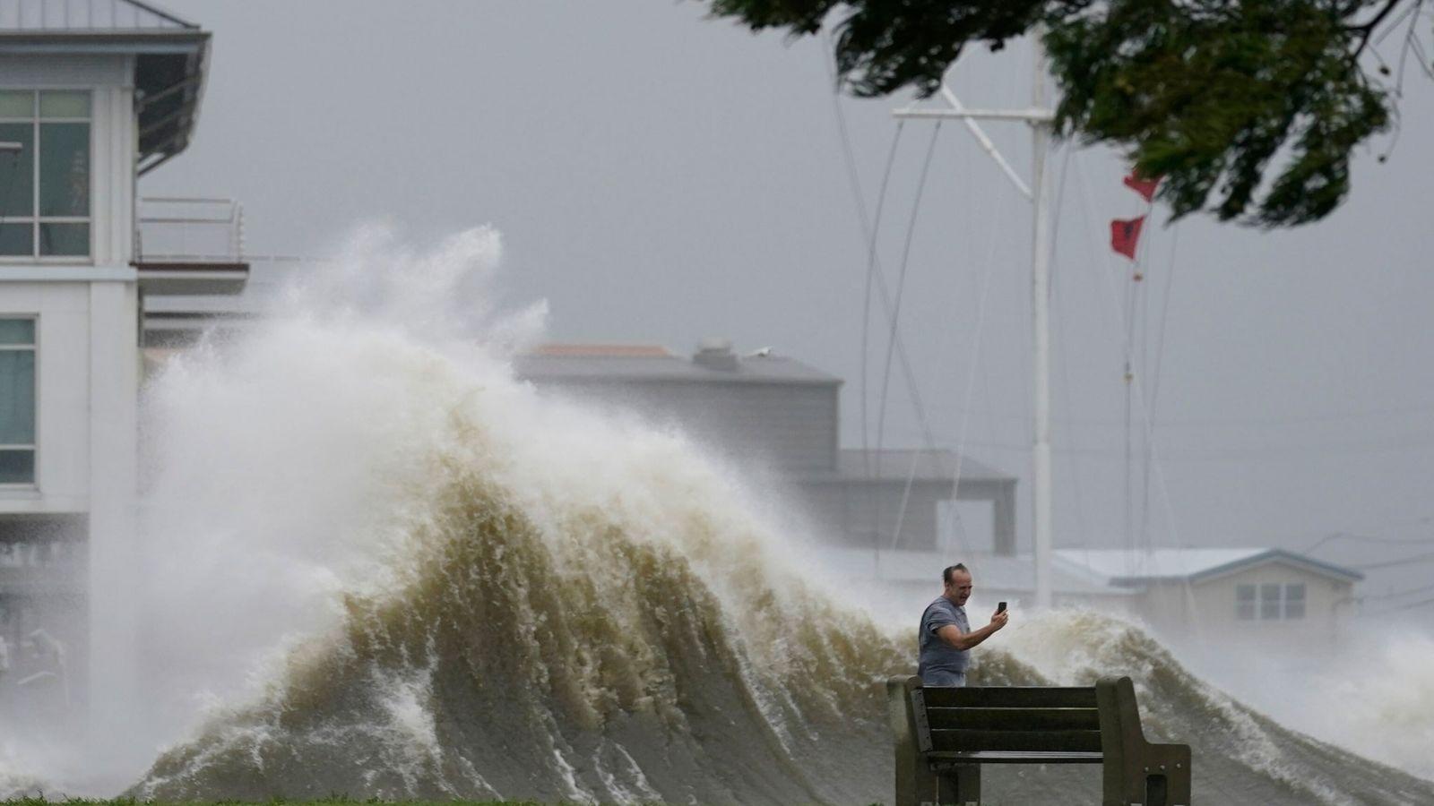 29 août 2021 : un homme photographie les immenses vagues avec son téléphone portable, sur le rivage du ...