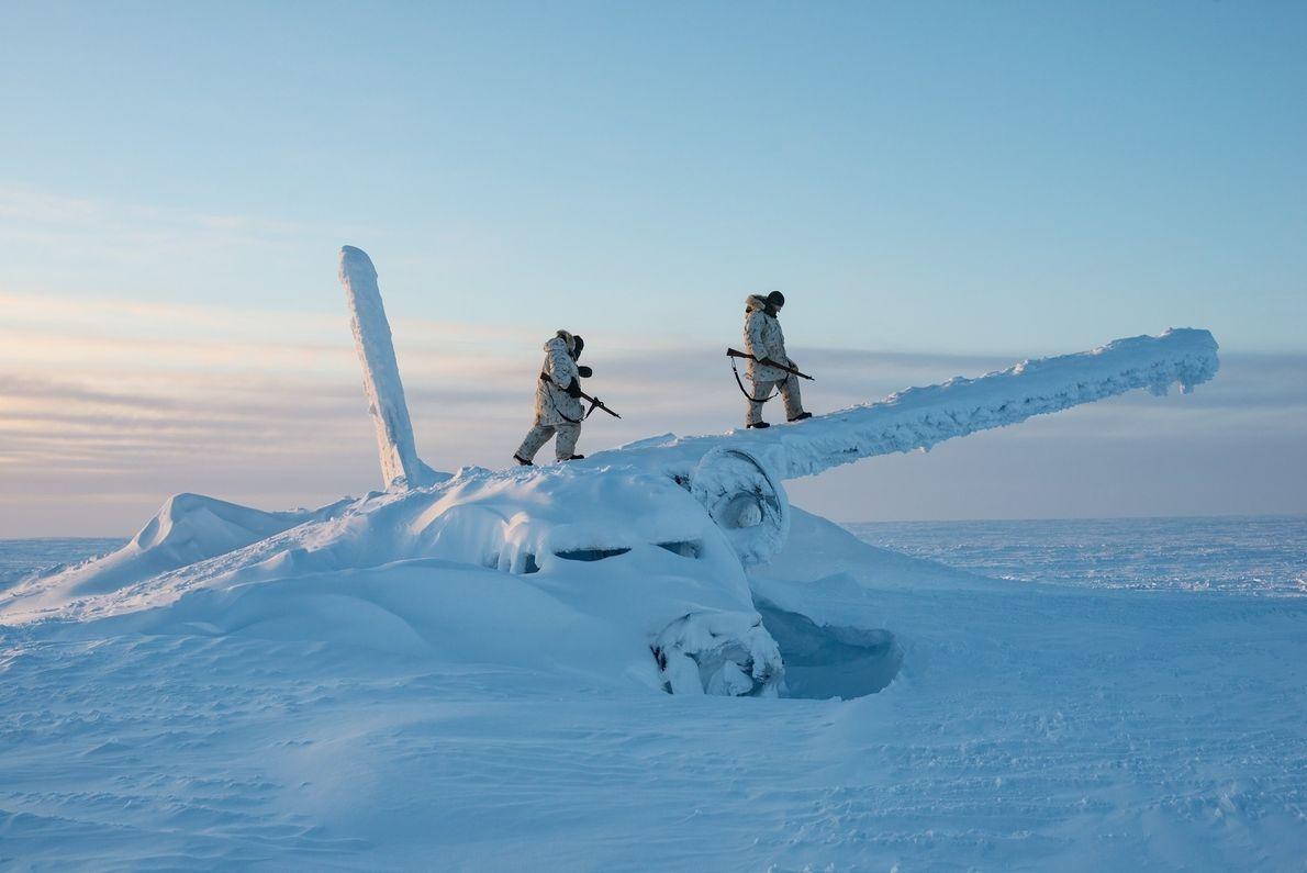 Des soldats canadiens grimpent sur la carcasse d'un avion, à environ 1 600 km du pôle ...