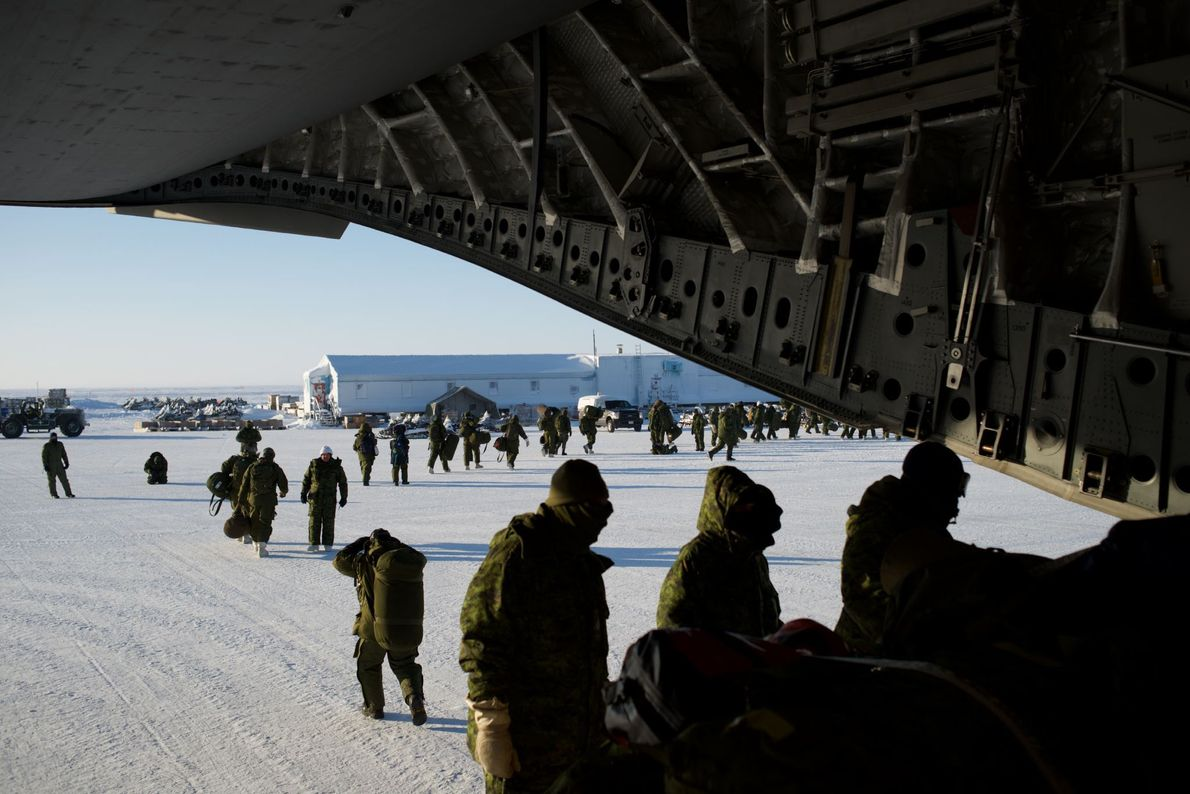 Au cours d'une mission d'entraînement à Hall Beach, au Nuvanut, des soldats canadiens débarquent d'un avion ...