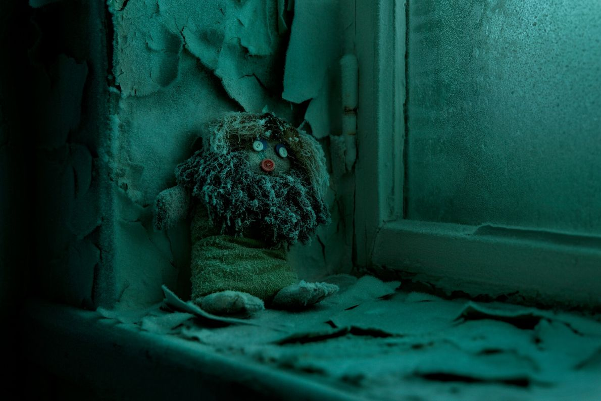 Une poupée appuyée sur le mur gelé d'un rebord de fenêtre dans une école abandonnée de ...