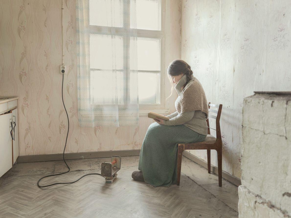 Kostikova se réchauffe près d'un petit radiateur en lisant un livre. Enfant, un ami de sa ...