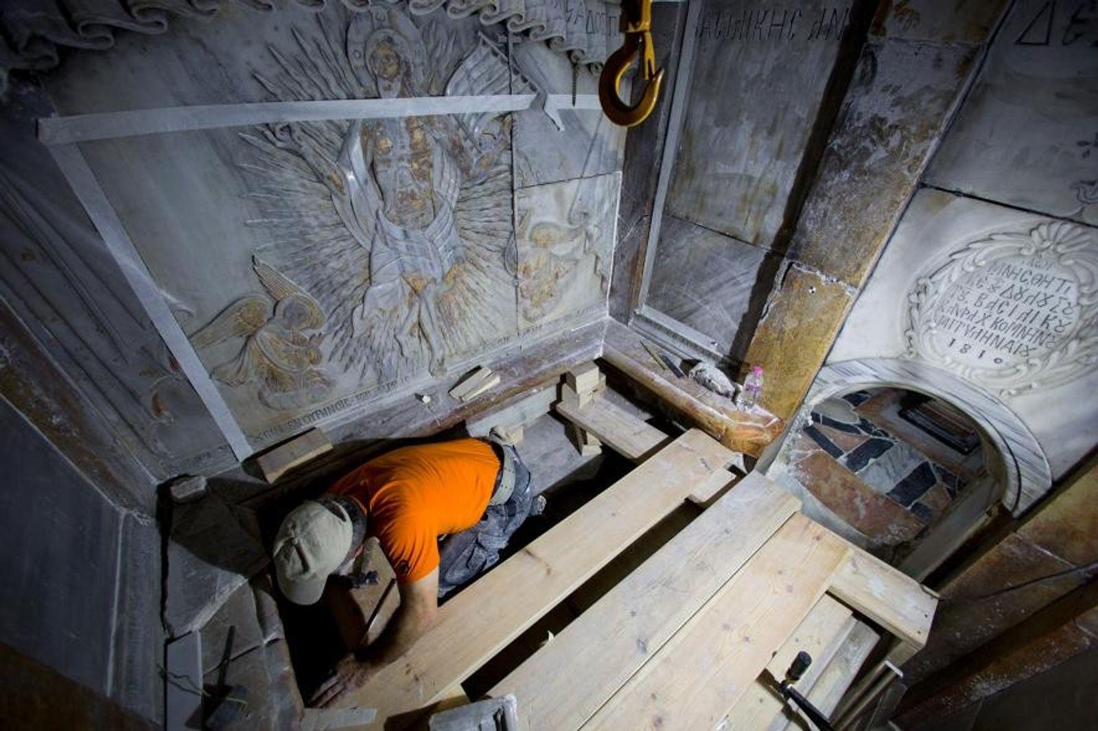 Un conservateur nettoie la surface de la stèle de pierre qui abriterait le lieu de sépulture ...