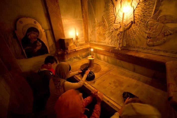 Des fidèles chrétiens prient à l'intérieur du tombeau de Jésus, situé au sein de l'église du ...