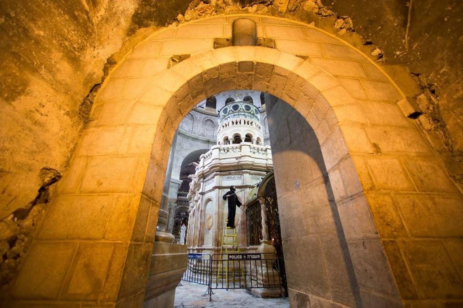 Un moine copte dépoussière la façade d'une chapelle située derrière l'édicule.