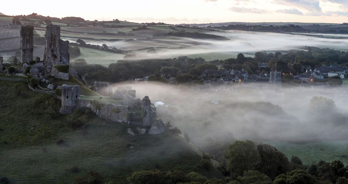La brume enveloppe le village de Corfe Castle, dans le Dorset, en Angleterre, à l'aube du ...