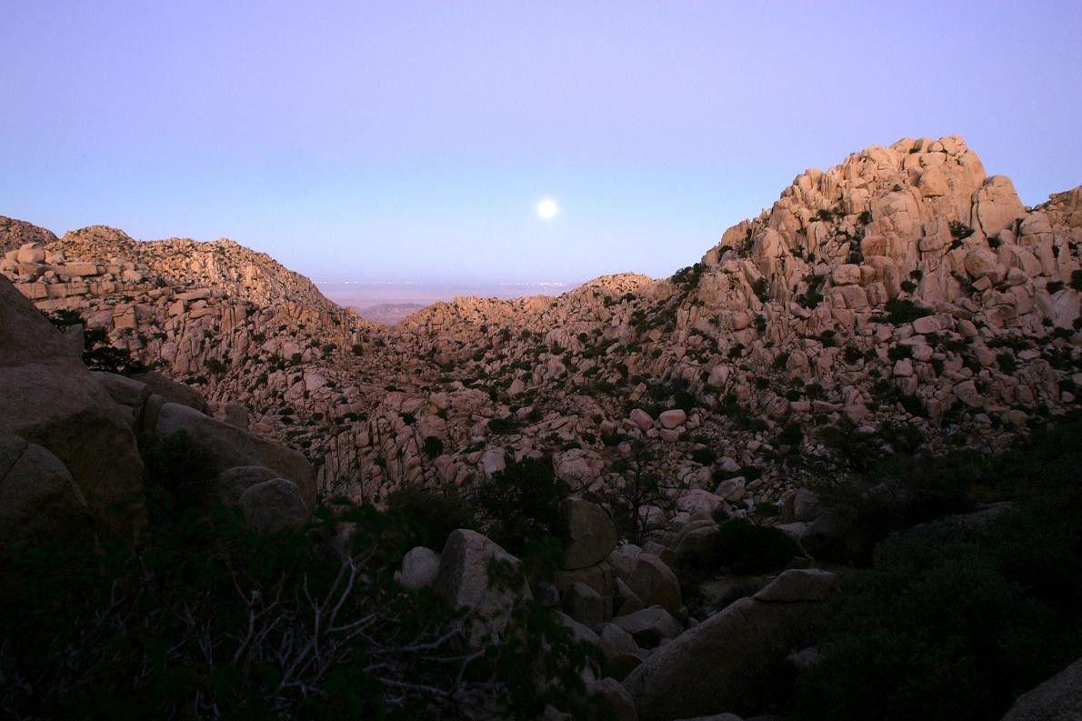 Une pleine lune marque l'équinoxe automnal alors qu'elle s'élève au-dessus d'un paysage de montagne désertique constitué ...
