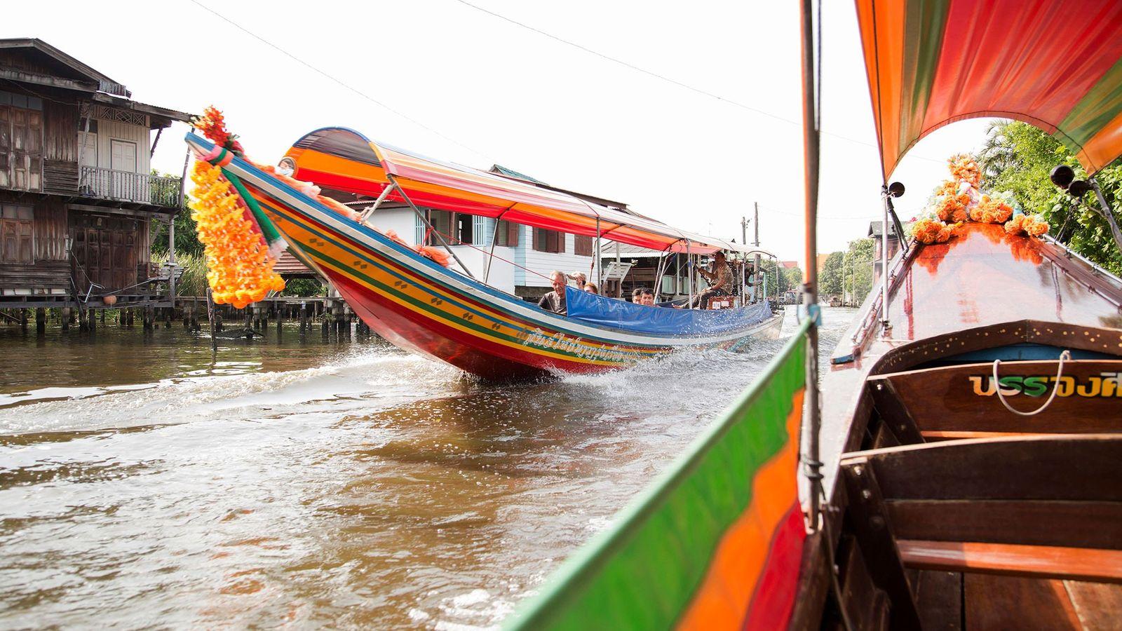 À Bangkok, des bateaux colorés naviguent sur le fleuve Chao Phraya. Avec l'urbanisation, certaines communautés et ...
