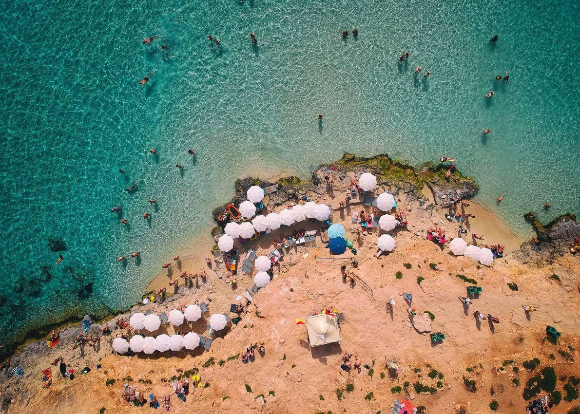 Les nageurs s'immergent dans les eaux turquoise d'une plage située entre les îles maltaises de Comino ...