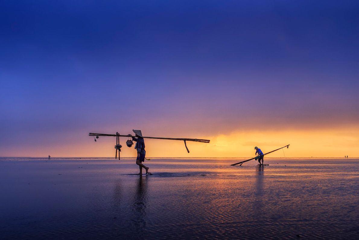Des pêcheurs transportent piquets et filets sur leur épaule alors qu'ils pataugent dans les eaux acheminées ...