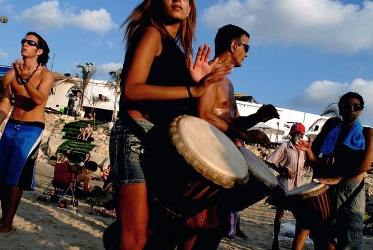 Photo : Hommes et femmes jouent du tambour sur la plage
