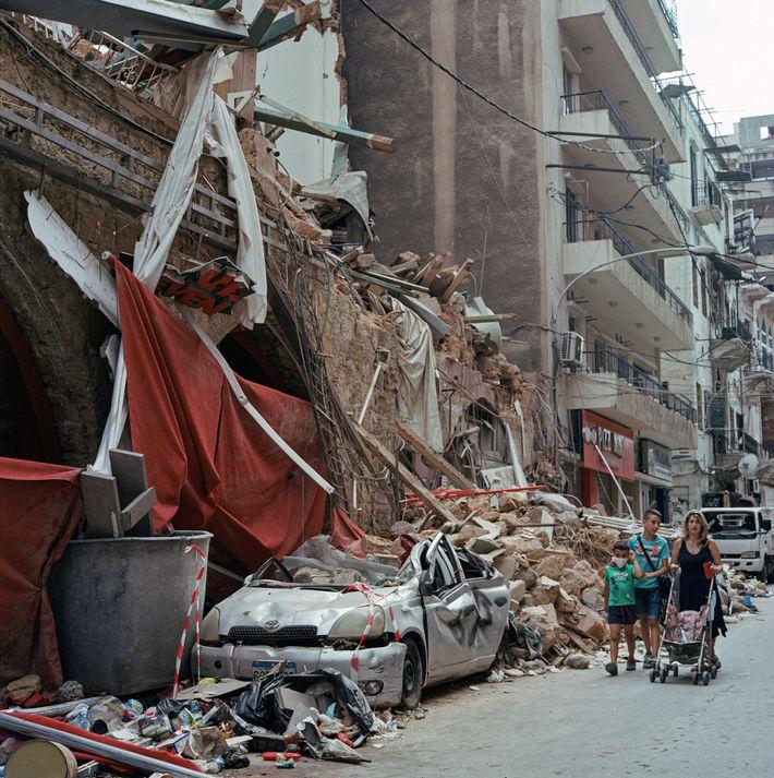 Des piétons passent à côté d'un immeuble effondré dans le quartier de Mar Mikhael à Beyrouth, au ...