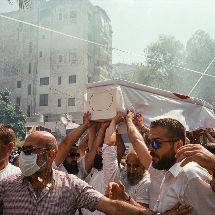 Porté par ses camarades, le cercueil du jeune pompier Ralph Mellehe fait le tour du quartier. ...