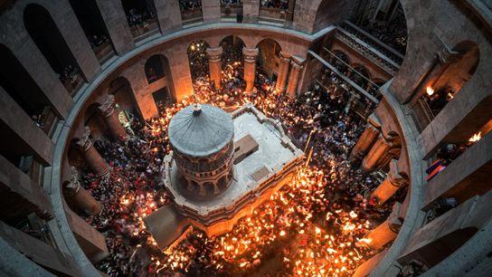 Dans l'église du Saint-Sépulcre, à Jérusalem, des croyants se pressent autour de l'Édicule restauré. Selon la ...