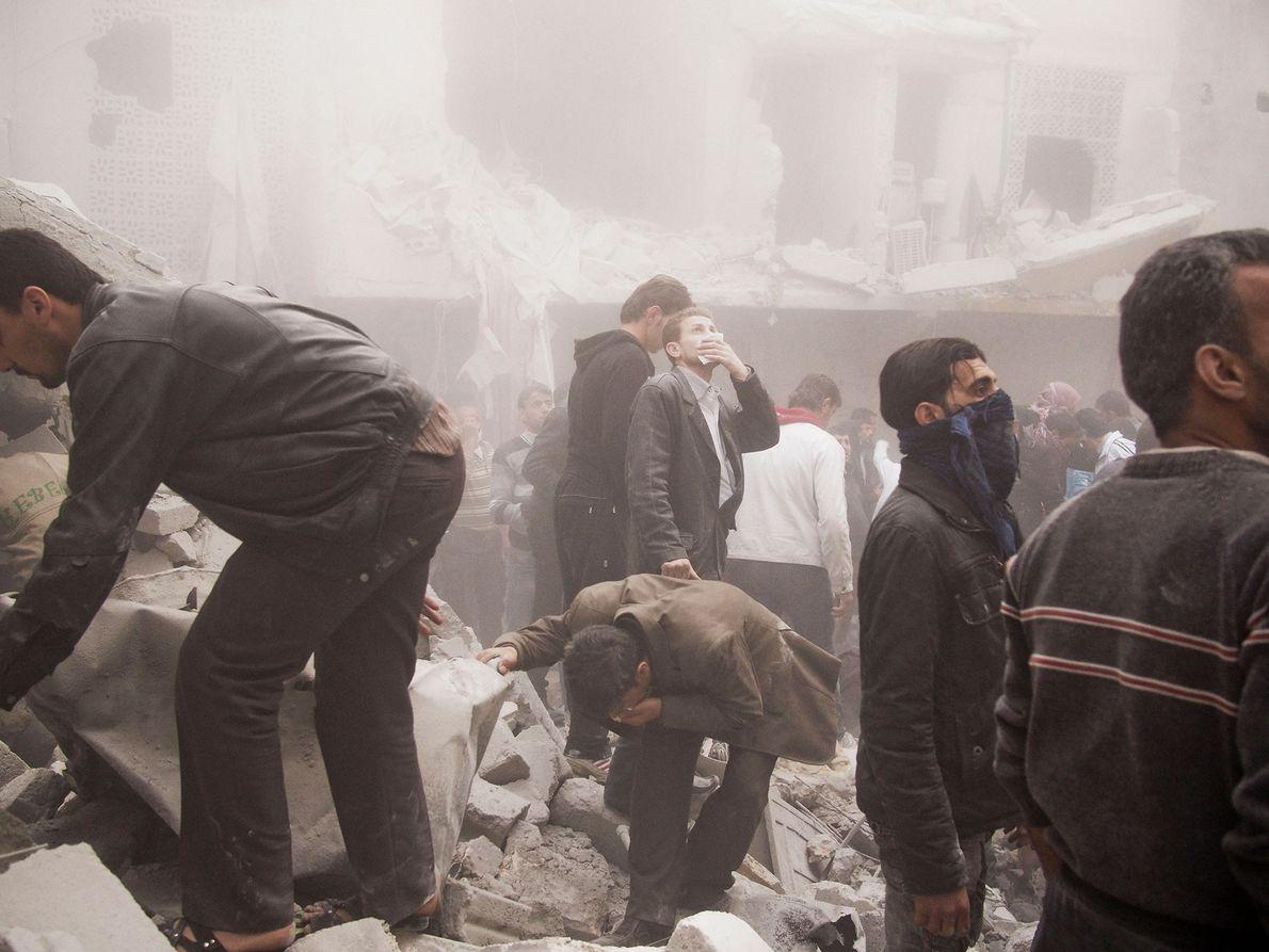 19 mars 2013, Alep en Syrie. Dans le quartier d'Al-Sukri, des habitants d'un bâtiment résidentiel émergent ...