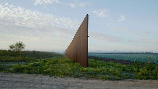 Un mur en acier traverse des terres agricoles, près de Brownsville (Texas). Érigée un peu au ...