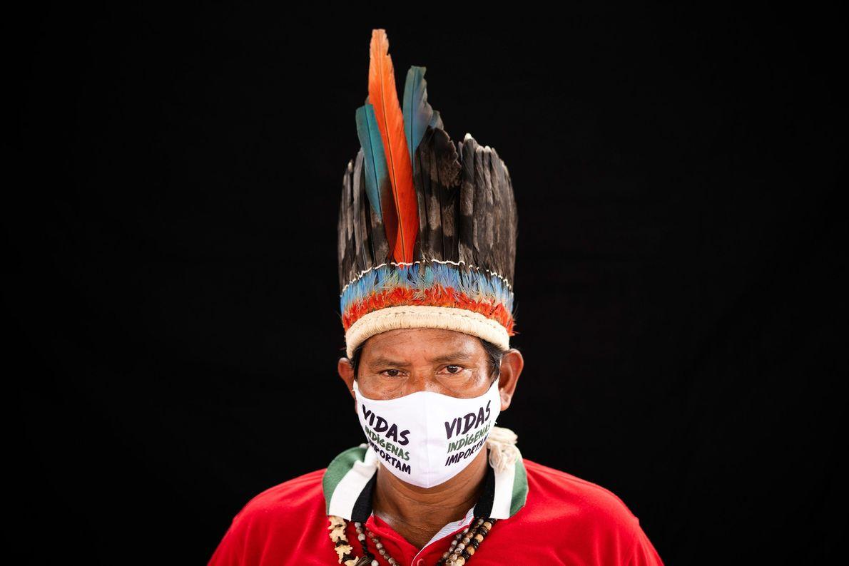 Le chef d'une tribu Miranha porte une coiffe traditionnelle et un masque portant la mention « Vidas ...