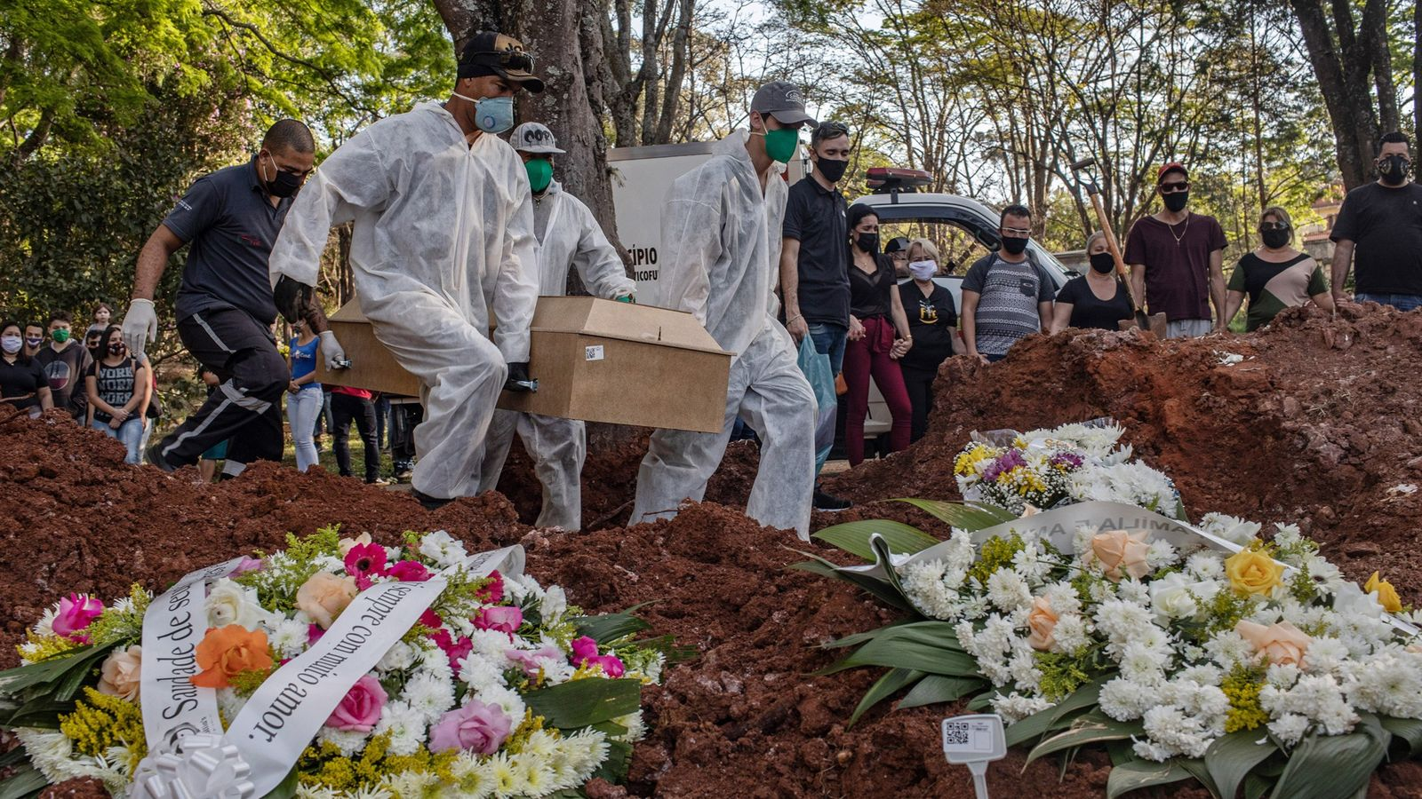 Équipés d'une combinaison, des fossoyeurs enterrent une victime du coronavirus au cimetière de Vila Formosa, à ...