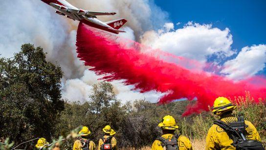 Un avion largue du retardant pour ralentir la progression des flammes de l'El Dorado. Au cours ...