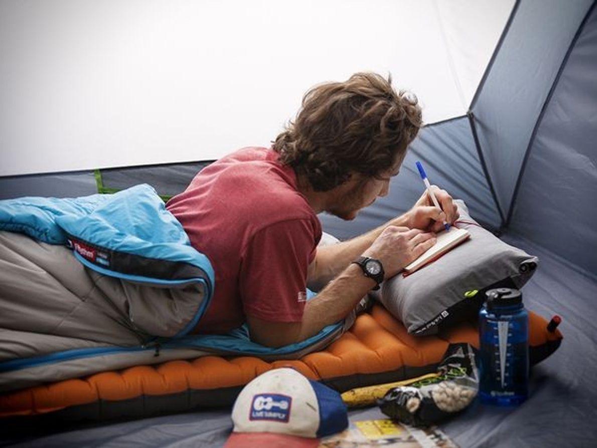 Photo d'un homme écrivant dans son carnet, à l'abri dans sa tente