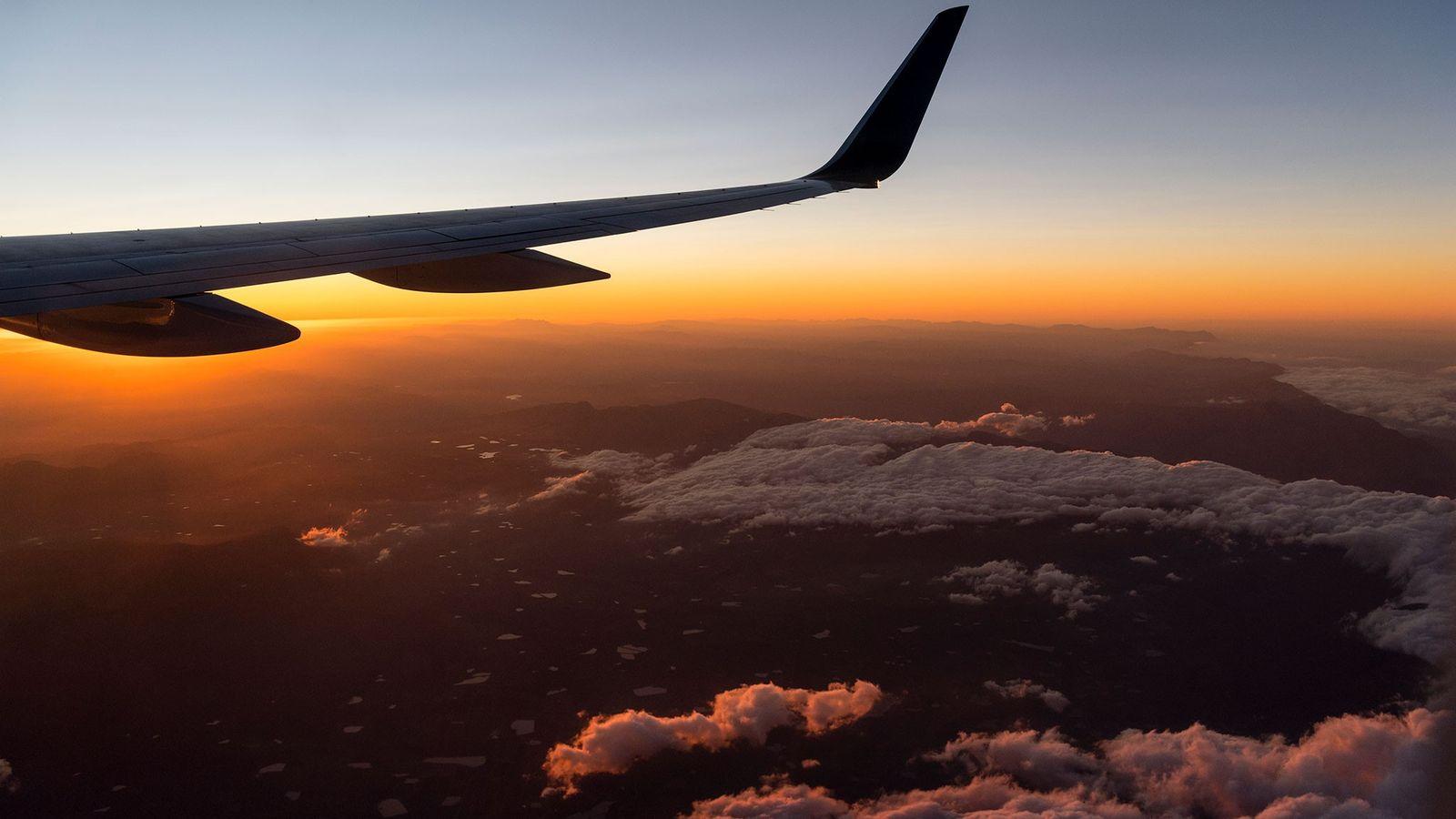 Un avion file en direction d'un lever de soleil éclatant au-dessus de Cape Town, en Afrique ...