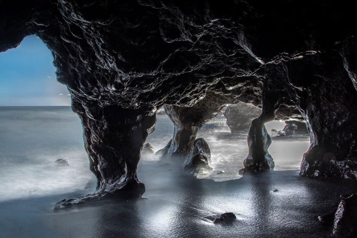 Les rayons de soleil dessinent les contours des parois noueuses d'une grotte de calcaire sur une ...