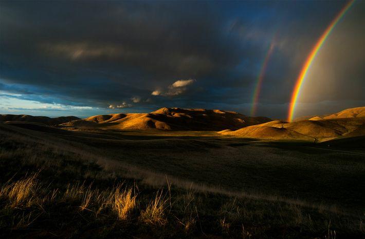 À la fin du printemps en Californie, deux arcs-en-ciel fendent le ciel des montagnes de San ...