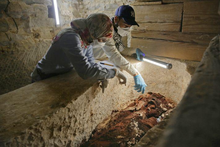 Les archéologues Maysa Rabeeh et Mohammed Refaat examinent le cercueil en bois vermoulu d'un prêtre nommé ...