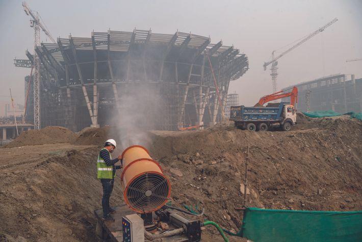 Sur un chantier, à Delhi, une machine vaporise de l'eau pour empêcher la poussière de voler. ...