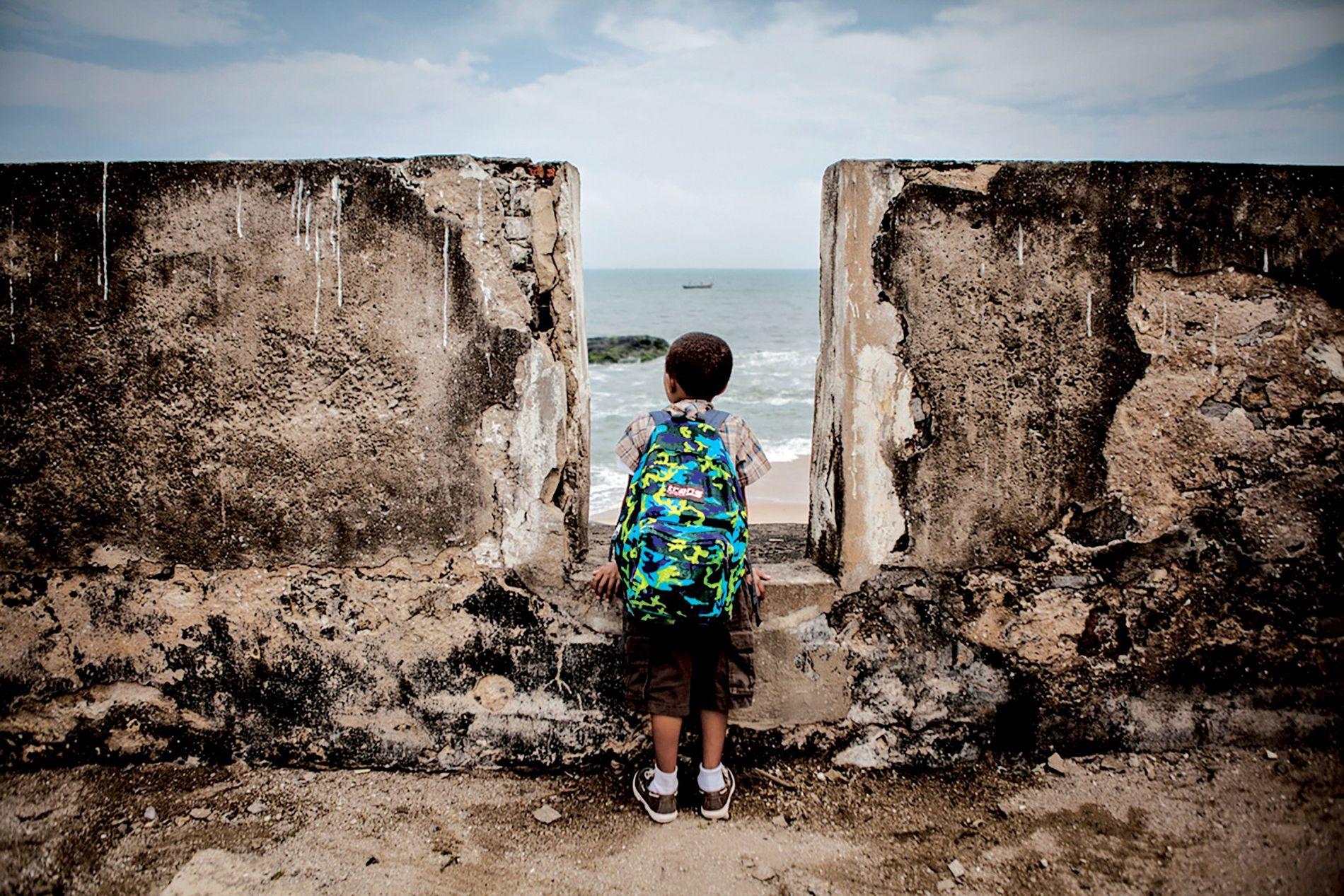 Un jeune touriste américain issu de la 11e génération de descendance des esclaves scrute l'horizon depuis Fort William au Ghana, l'un des points de départ de la traite négrière transatlantique.