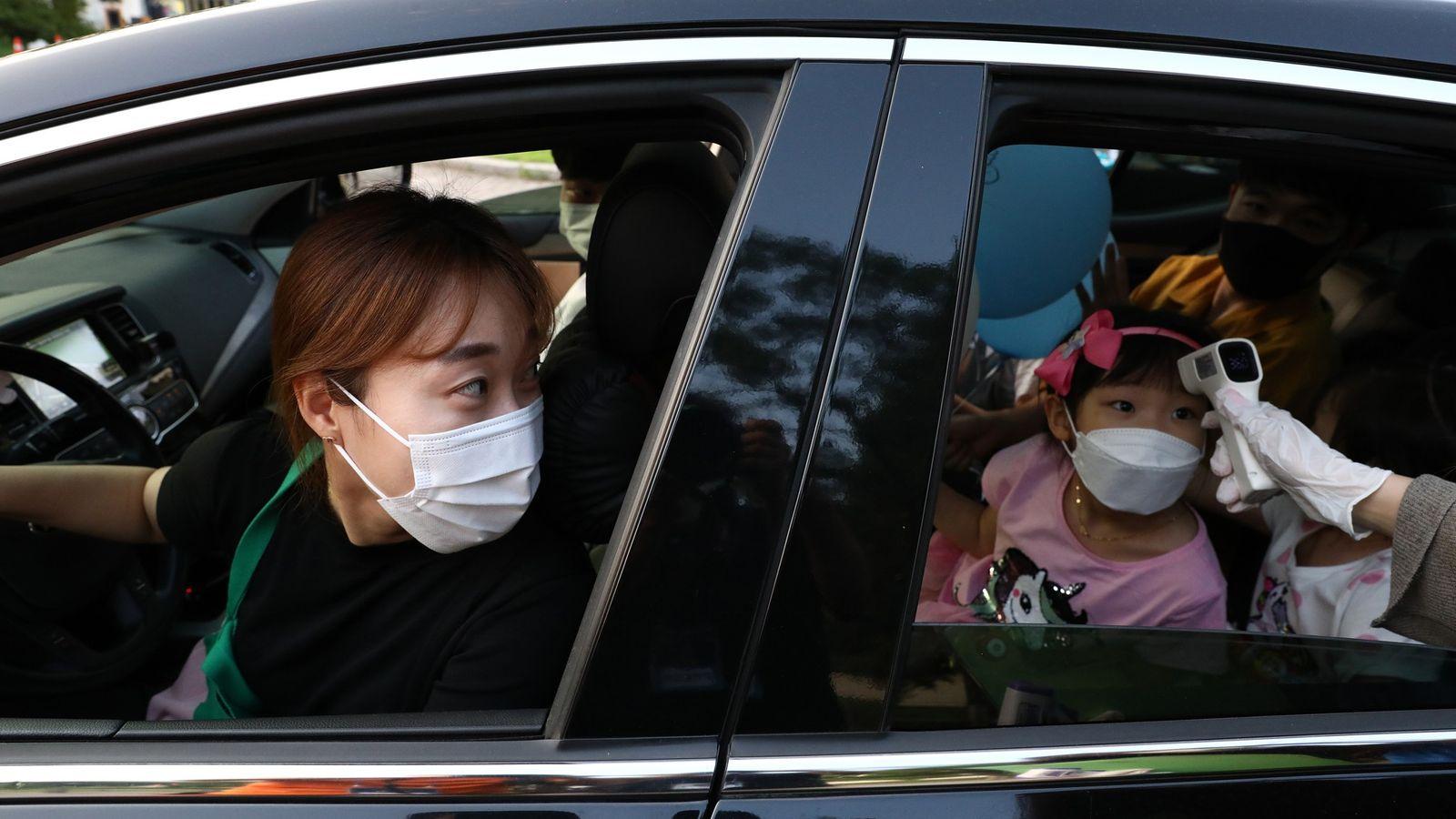 Prise de température au drive d'une clinique sud-coréenne pour cette jeune fille sous les yeux attentifs ...