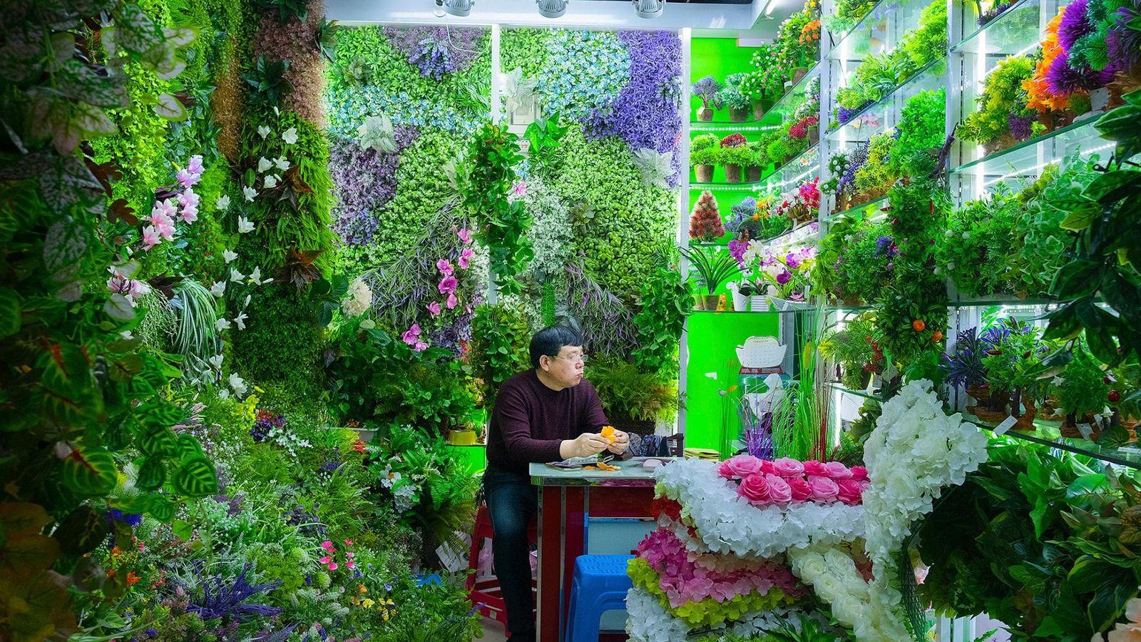 Au marché central, un commerçant est assis à son étal, où il vend en gros des ...