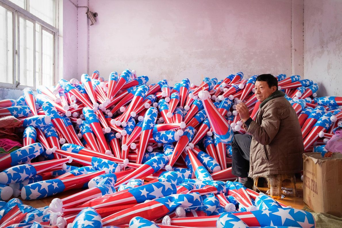 Un ouvrier se trouve dans une usine confectionnant des massues en plastique pour les enfants.