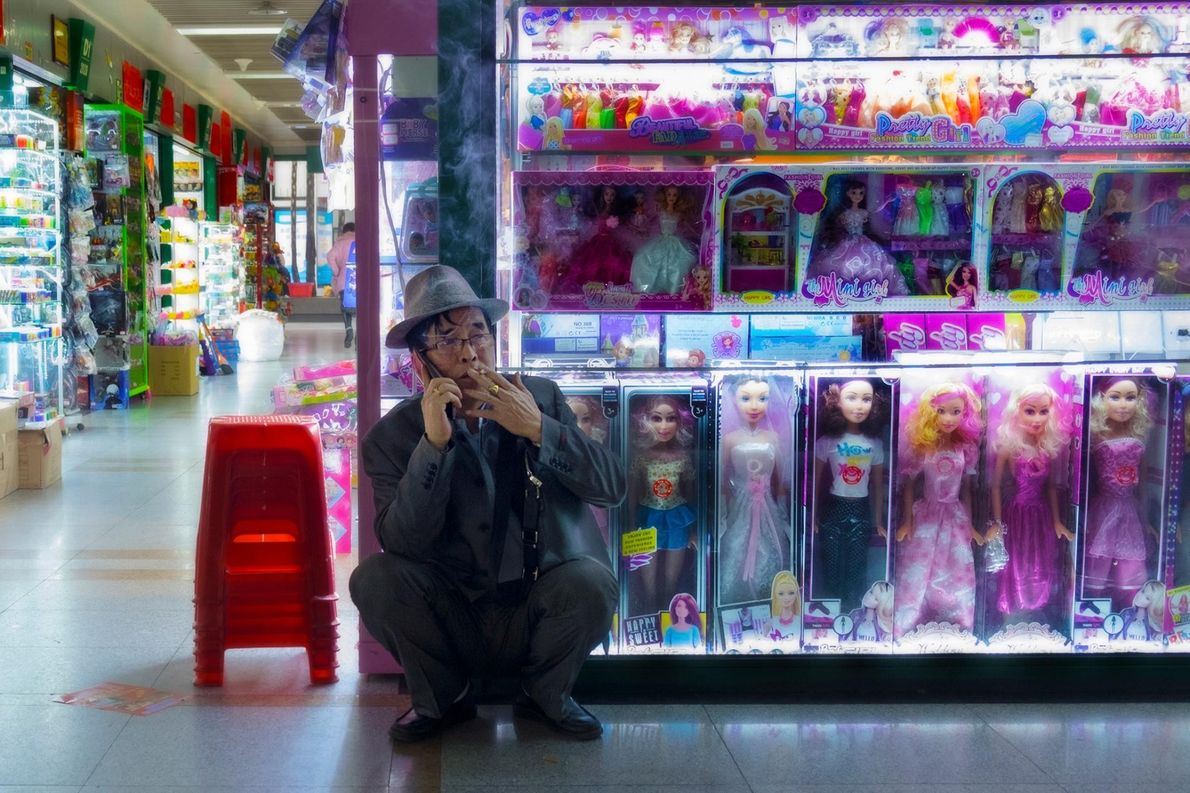 Un homme d'affaires fume une cigarette dans le département des jouets du marché central.