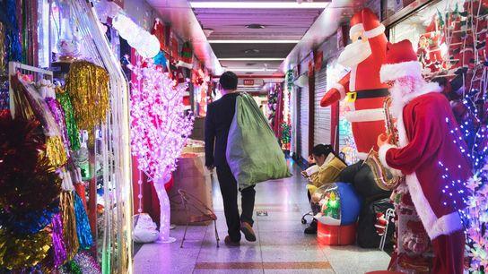 Un homme collecte différents objets dans plusieurs magasins du « département de Noël » du marché ...
