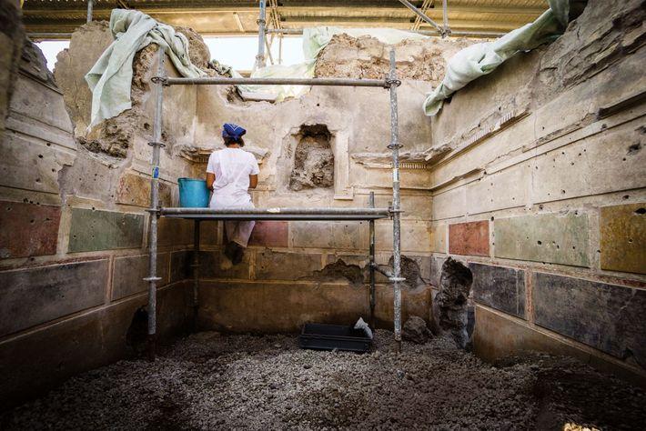 Dans la maison d'Orion nouvellement découverte, un restaurateur nettoie les panneaux de stuc peint qui ressemble ...