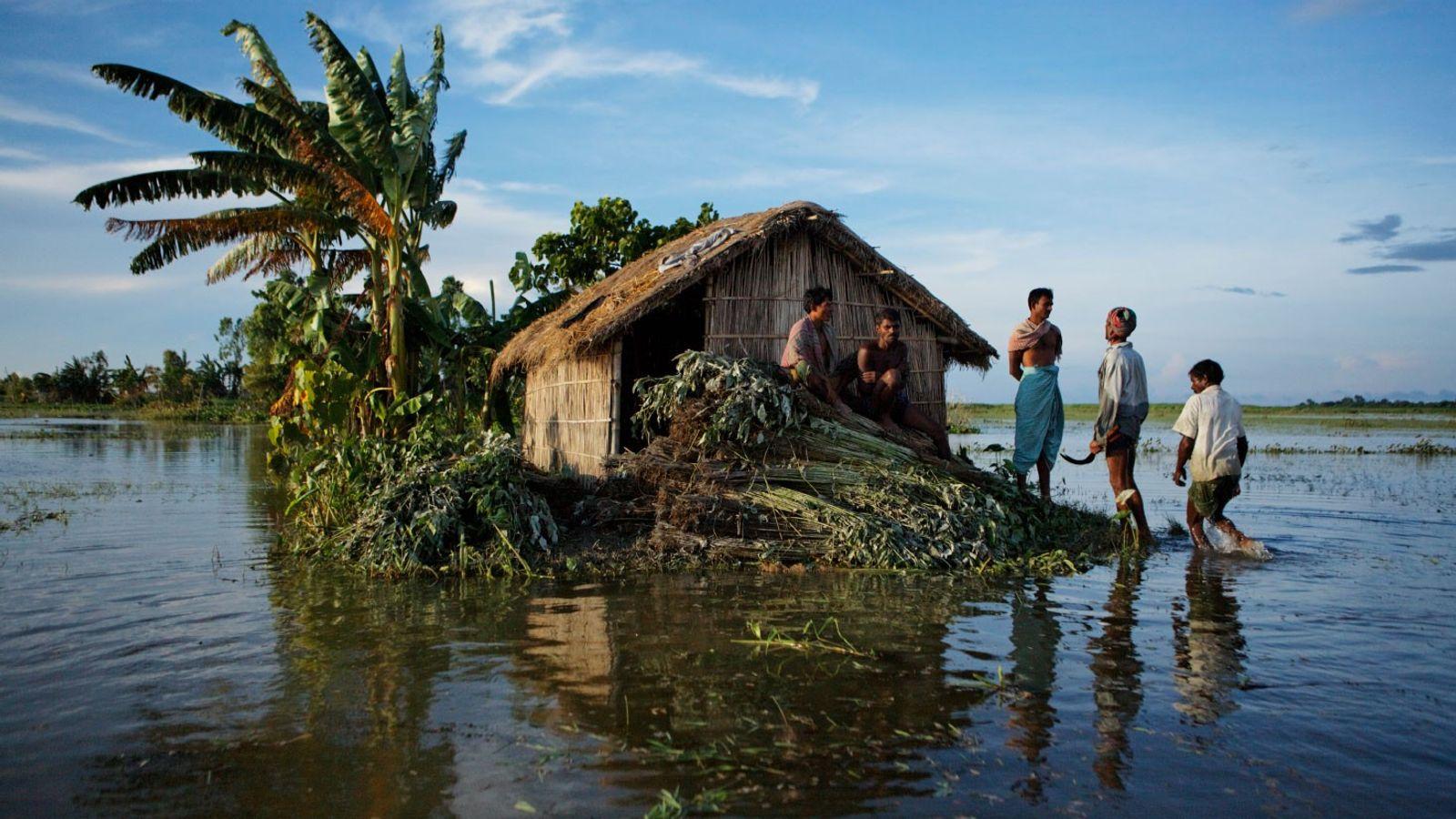Des villageois se tiennent debout sur le paillage de jute d'une maison inondée dans le district ...