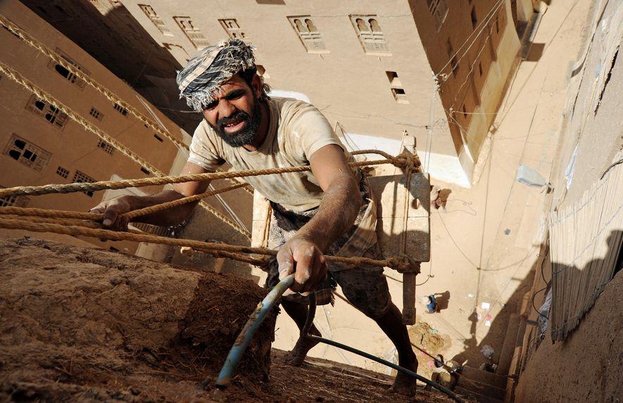 Un homme réalise des travaux d'entretien pour préserver les bâtiments en torchis de Shibam.
