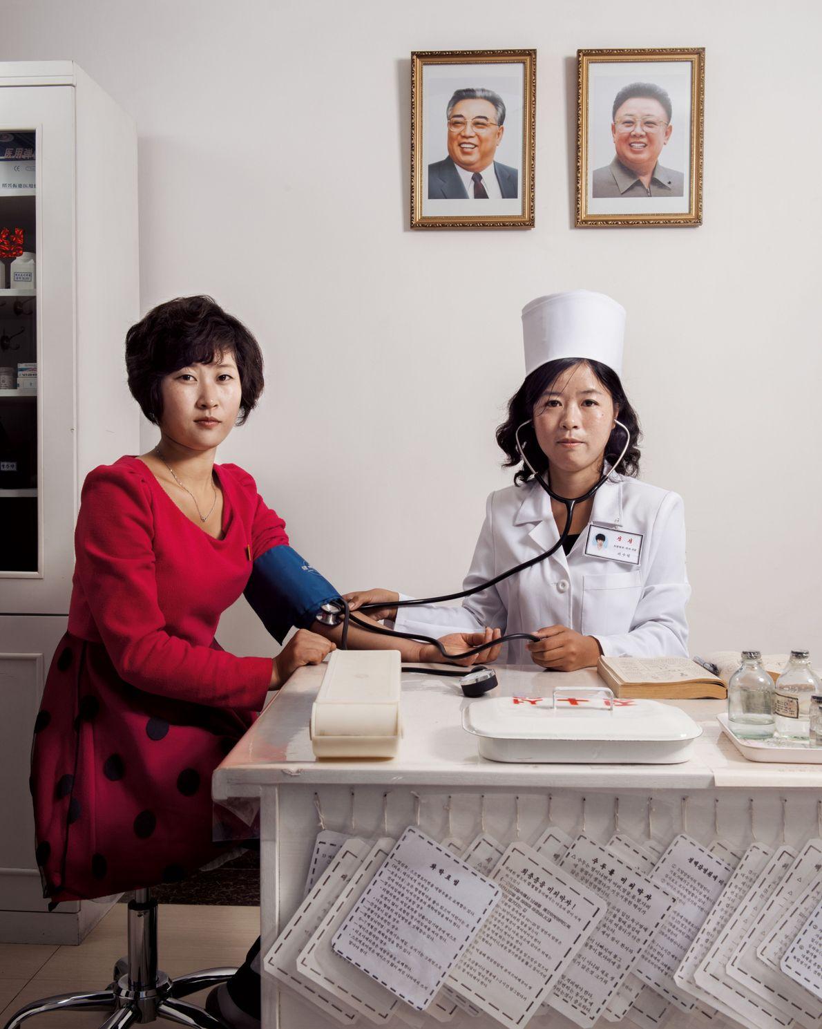 Une femme médecin ausculte une ouvrière dans la plus grande usine textile de Corée du Nord. ...