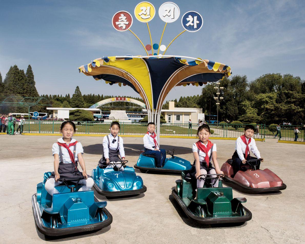 Des enfants jouent dans des autos tamponneuses, à la fête foraine de Mangyongdae, près de la ...