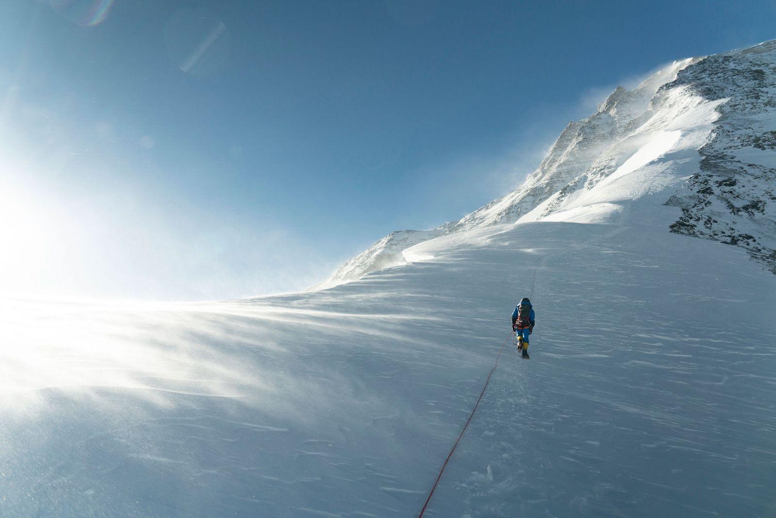 Un alpiniste progresse par temps venteux sur l'itinéraire classique de l'arête nord, sur le versant tibétain/chinois ...