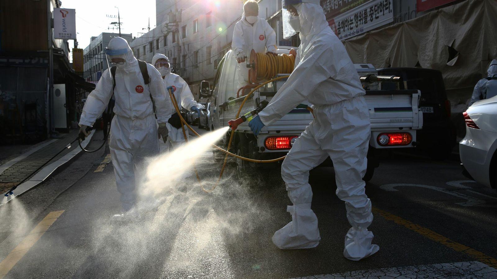 Le 6 octobre, des agents de désinfection équipés de protections individuelles nettoient une rue de la vile ...