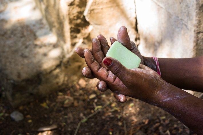 Un enseignant montre à ses jeunes élèves comment se laver correctement les mains dans une école ...