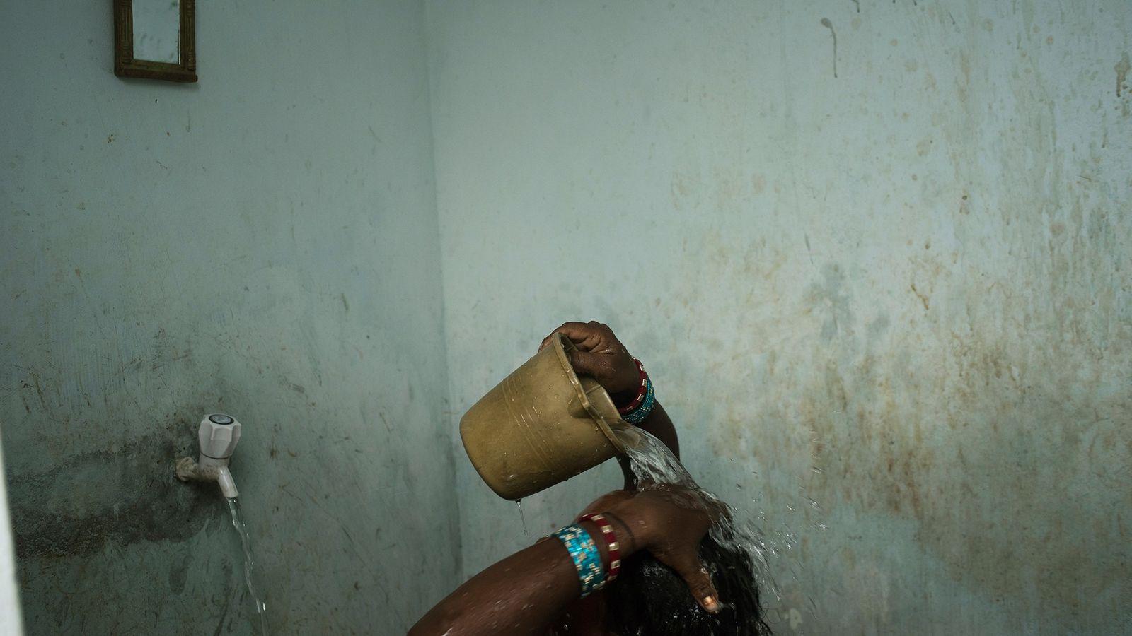 Une femme se lave près de Bhubaneshwar, une ville de l'état d'Odisha dans l'est de l'Inde. ...