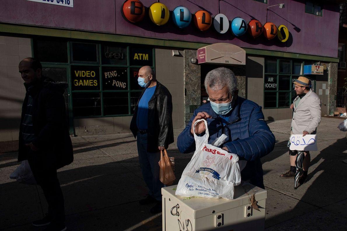 Quelques personnes attendent leur tour pour bénéficier de repas gratuits dans le quartier Bay Ridge de ...