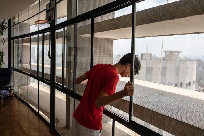 Âgé de 14ans, Daniel Sabino jette un œil en dehors de l'immense appartement de sa famille ...