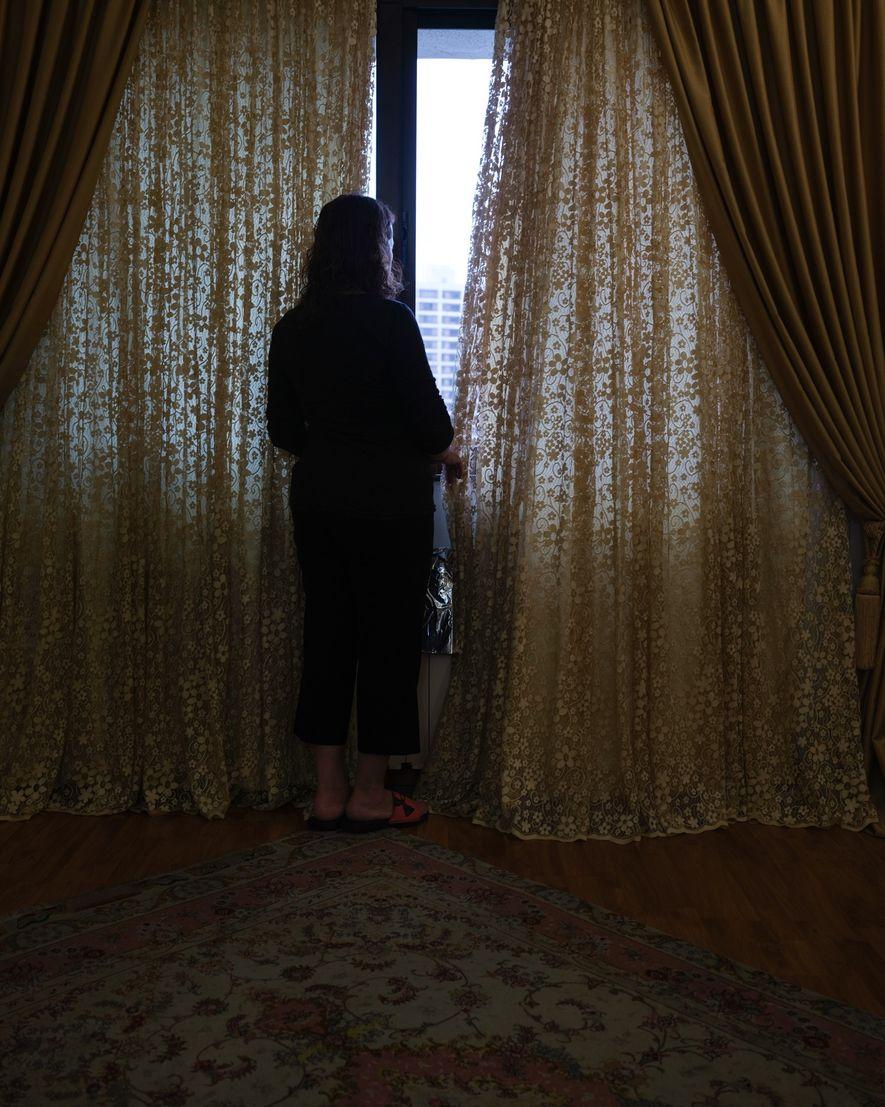 La mère de l'auteure, Jila, se tient devant la fenêtre de sa chambre pour scruter l'arbre ...